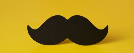 closeup of a black moustache on a yellow background