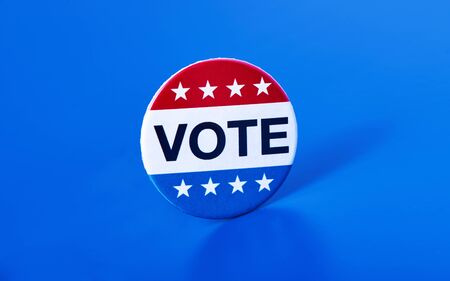 closeup of a vote badge for the United States election on a blue background Foto de archivo