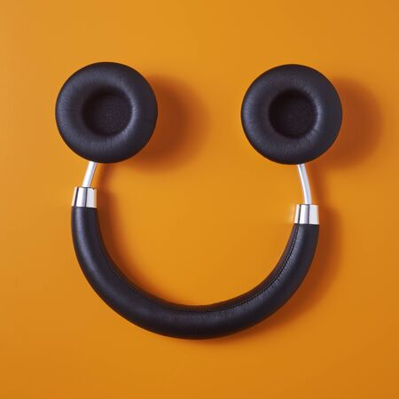high angle view of a pair of black wireless full size headphones upside down on an orange background, resembling a smiley face Reklamní fotografie