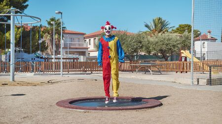 Scary clown wearing a colorful yellow, red and blue costume, bouncing on a trampoline in an outdoor public playground