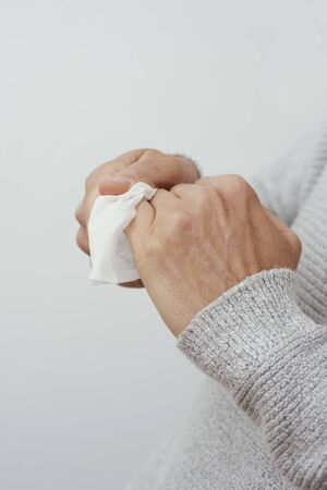 closeup of a caucasian man, wearing a casual pale gray sweater, disinfecting his hands with a wet wipe