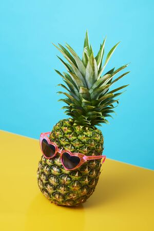 a pineapple wearing a pair of pink heart-shaped sunglasses on a blue and yellow background