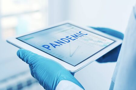 closeup of a doctor man, wearing blue surgical gloves, having a digital tablet in his hands with the word pandemic in its screen