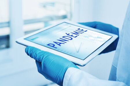 closeup of a doctor man, wearing blue surgical gloves, having a digital tablet in his hands with the word pandemie, pandemic written in french, n its screen
