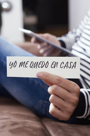 closeup of a man, in casual wear indoors, showing the message I stay at home in spanish written in a piece of paper, as a measure to stop the spreading of the covid-19