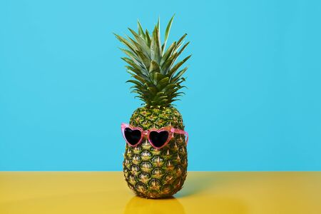 a pineapple wearing a pair of pink heart-shaped sunglasses on a yellow surface against a blue background with some blank space