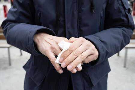 A caucasian man on the street disinfecting his hands with a wet wipe