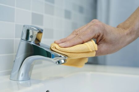closeup of a caucasian man cleaning the faucet of a sink with a microfiber cloth Banque d'images
