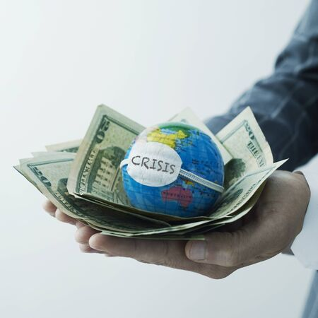businessman holding a world globe with a protective mask, with the word crisis written in it, on top of a handful of dollar bills