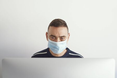 closeup of a young caucasian man indoors, wearing a surgical mask, using a computer