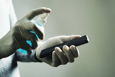 Closeup of a caucasian man, wearing latex gloves, disinfecting his smartphone by spraying a sanitizer from a white bottle