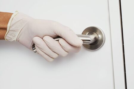 A caucasian man opening a door wearing latex gloves, as a measure to prevent the transmission of infections