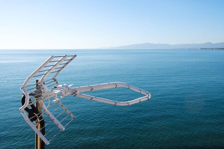 Top section of a television antenna, with a calm sea and the blue sky