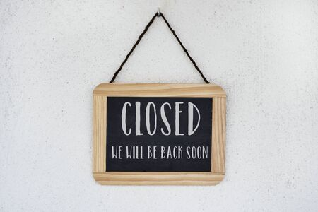 a wooden-framed chalkboard, with the text closed, we will back soon written in it, hanging from a white wall Banque d'images
