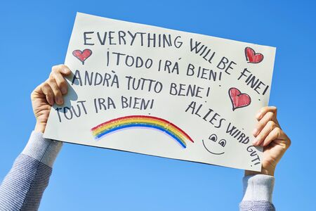 Man showing a homemade sign with the text everything will be fine in different languages Archivio Fotografico
