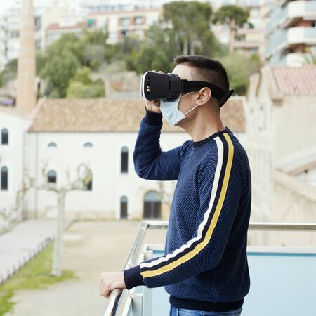 A caucasian man, wearing a surgical mask, using a virtual reality headset in a balcony