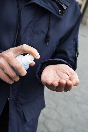 A caucasian man on the street disinfecting his hands with a blue hand sanitizer from a bottle Stock Photo