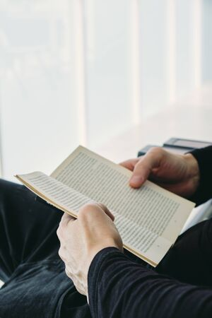 closeup of a young caucasian man, in casual wear, reading a book sitting in an outdoors armchair on the balcony