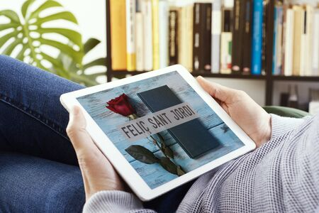man watching, in a tablet, a picture of a rose, a book and the text Happy Saint Georges Day written in Catalan, made by myself, when it is tradition to give red roses and books in Catalonia, Spain