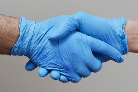closeup of two people, wearing blue surgical gloves, shaking hands against a gray background