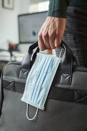closeup of a young man in an office holding a briefcase and a surgical mask in his hand Banque d'images