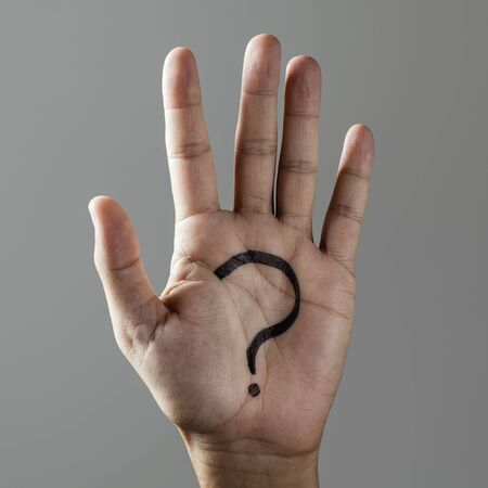closeup of the hand of a man with a question mark painted in his palm, on a gray background
