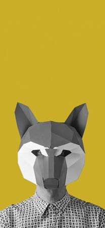 portrait of young caucasian man wearing a fox mask in black and white on a yellow background with some blank space on top, in a vertical format to use for mobile stories or as smartphone wallpaper