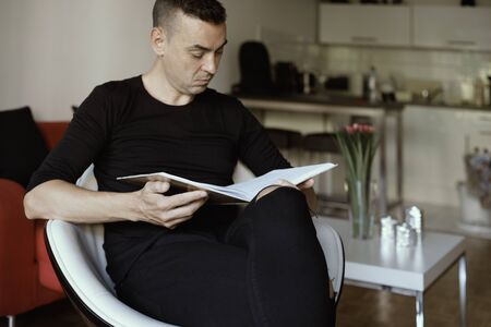 closeup of a young caucasian man, in casual wear, sitting in a white comfortable chair in the living room, reading a book Standard-Bild