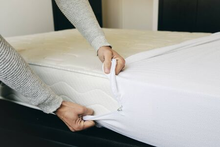 closeup of a young caucasian man covering a mattress with a white mattress protector
