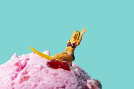 closeup of a miniature woman in swimsuit, kneeling on a surfboard, on a strawberry ice cream ball, against a blue background with some blank space