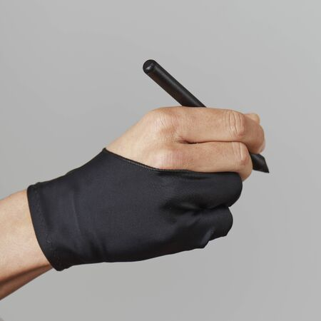 closeup of a caucasian man wearing a black two finger glove while holding a graphic pen in his hand, on a gray background