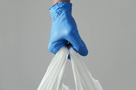 closeup of a man wearing blue latex gloves carrying a white shopping bag in his hand 스톡 콘텐츠