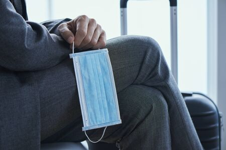 Close up of a young businessman sitting next to his suitcase in the waiting hall and holding a surgical mask in his hand