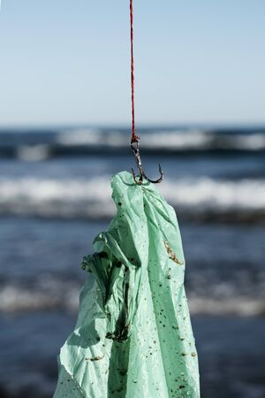 closeup of a used green plastic bag in a fish hook, freshly fished in the ocean