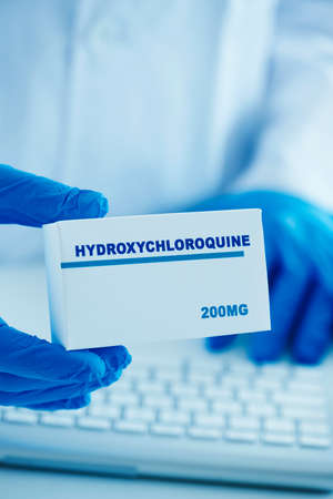 closeup of a man, wearing a white coat and blue surgical gloves, having a simulated box of hydroxychloroquine in his hands 版權商用圖片