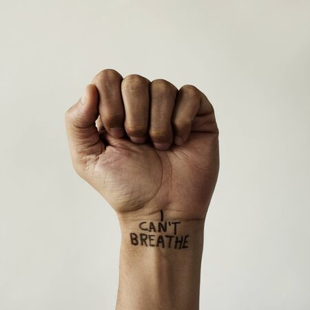 closeup of the raised fist of a man with the text I cant breathe in his wrist, as it is used as slogan in the protests in response to police brutality and racism in the United States