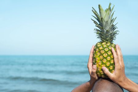 closeup of a man seen from behind on the beach, in front of the sea, holding a pineapple on his head, with some blank space on the left