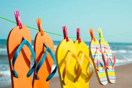 closeup of some different pairs of colorful flip-flops hanging on a clothes line on the beach, with the sea in the background