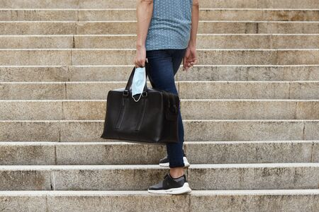 Closeup of a young man on the street carrying a black leather travel bag and a surgical mask in his hand Foto de archivo
