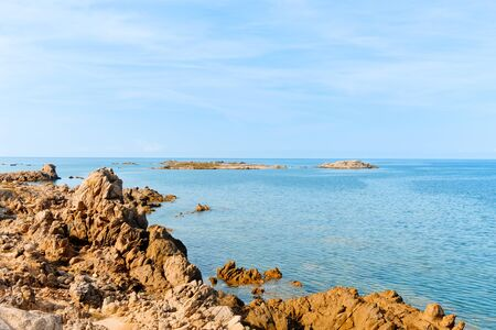a view of the rock formations in La Tonnara, on the Southern coast of Corsica, France, with the calm Mediterranean sea in the background Stock Photo
