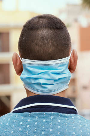 closeup of a man on the street, in casual wear, wearing his surgical mask in the back of his neck while is not wearing it in his face