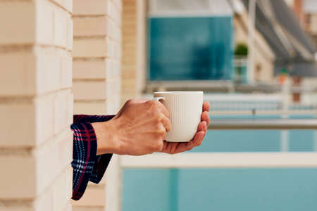 closeup of a young caucasian man, in pajamas, having a coffee leaning on the sill of a window, at his house or of a hotel