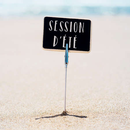 closeup of a black sign, with the text summer courses and/or summer school written in french, stuck on the sand of a quiet beach, with the sea in the background