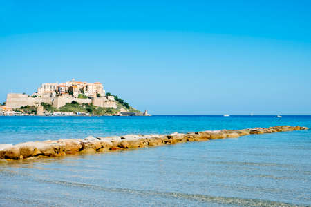a view of Calvi, in Corsica, France, with its famous citadel on the rigth on the top of a promontory, and the Mediterranean sea in the foreground