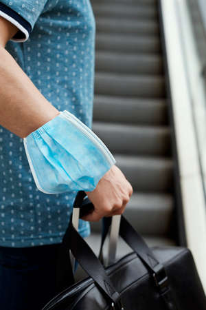 closeup of a young man on a scalator, in casual wear, carrying a travel bag in one hand and a suitcase in the other hand, wearing a surgical mask in his arm while is not wearing it in his face Reklamní fotografie