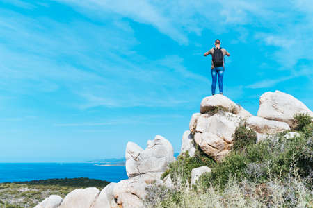 a young caucasian man, seen from behind, wearing jeans and a t-shirt and carrying a backpack, on the top of a rock formation, taking a photo of the sea in the Southern coast of Corsica, in France