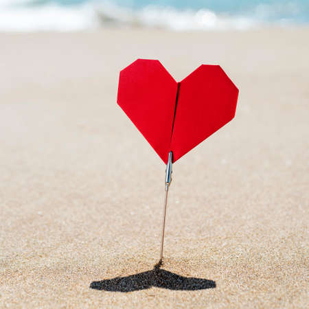closeup of a red origami hart stuck on the sand of a quiet beach, with the sea in the background