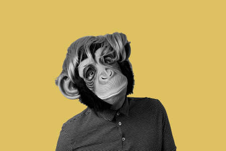 man wearing a monkey mask and a wig, in black and white, on a yellow background with some blank space around him
