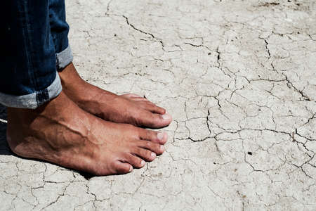 closeup of the feet of a young caucasian man, wearing jeans, on a cracked dry soil