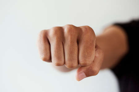 closeup of the fist of a young caucasian man throwing a punch to the observer or fist bumping, on a white background Zdjęcie Seryjne